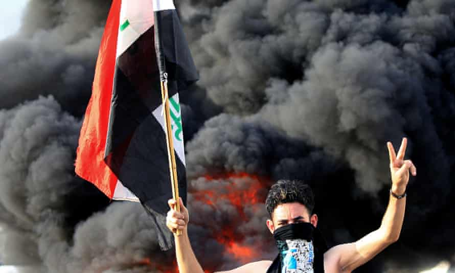 A demonstrator gestures as he stands close to burning tyres