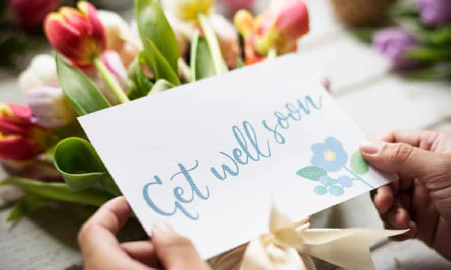 A get well soon card and bunch of flowers.