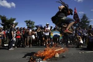 A student jumps over a burning effigy of Brazil's President Jair Bolsonaro.