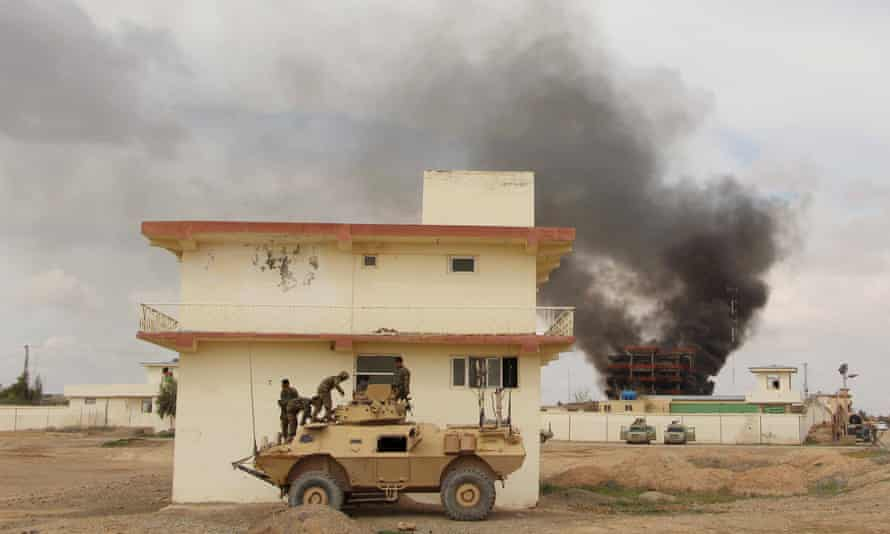 Smoke billows from a building after a Taliban attack in the Gereshk district of Helmand