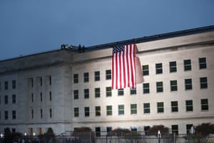 Stars and Stripes flag is unfurled over top  of building