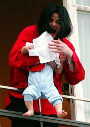 Michael Jackson shouts to fans as he dangles his nine-month-old son, Blanket, over the edge of his hotel balcony in Berlin, in November 2002.