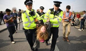 A climate activist is carried away by police on Waterloo Bridge