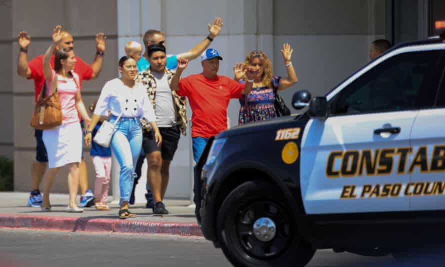 Shoppers exit with their hands up after the shooting