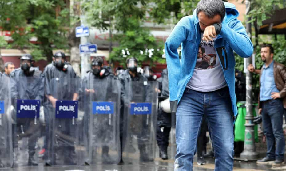 Veli Saçılık stands in front of a line of riot police after tear gas was used to disperse protesters.