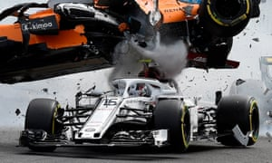 Fernando Alonso's McLaren flies over Charles Leclerc's Sauber at Spa. Alonso's car left black marks on Leclerc's halo safety device.