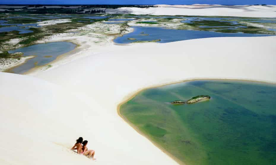 Two women ride a board down a sand dune at Dunas Tatajuba, just outside of Jericoacoara.