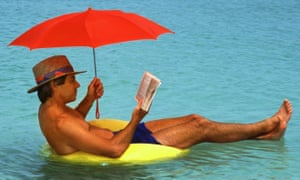 Middle-aged man with umbrella floating on tube in Caribbean reading book