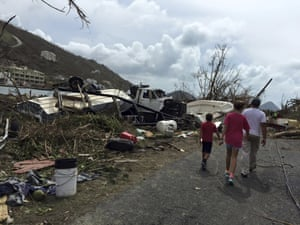 Residents walk past damaged caused by Hurricane Irma in Tortola in the British Virgin Islands.