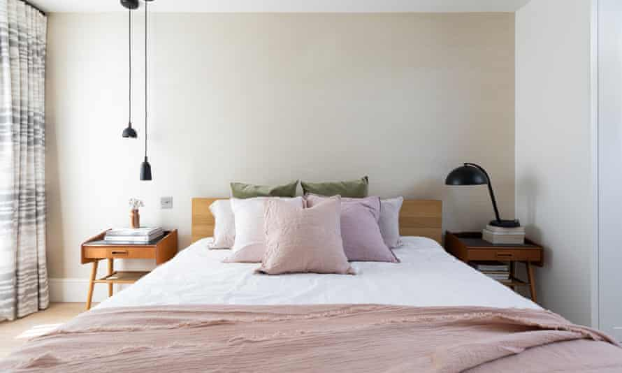 A bed with a pink bedspread and multiple pillows in the bedroom