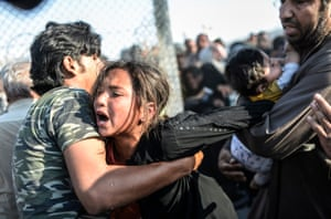 Spot News, third prize, stories - Bulent Kilic - Broken border: a man holds a crying girl as others rush through broken down border fences to enter Turkey