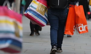 A shopper carrying bags along Oxford Street in London.