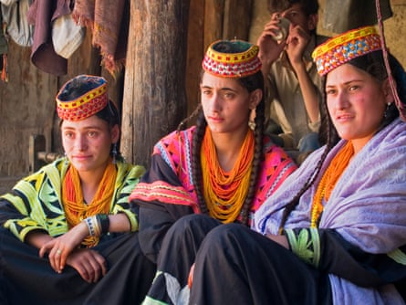 Three Kalasha sisters sitting together Rumbur Valley, Chitral, Pakistan