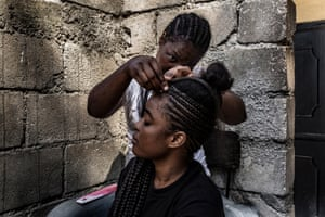 A woman braids the hair of her neighbour