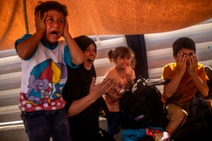 A migrant woman and children react after police fired tear gas during protests near Mytilene.