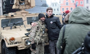 A man poses with a member of the US army.