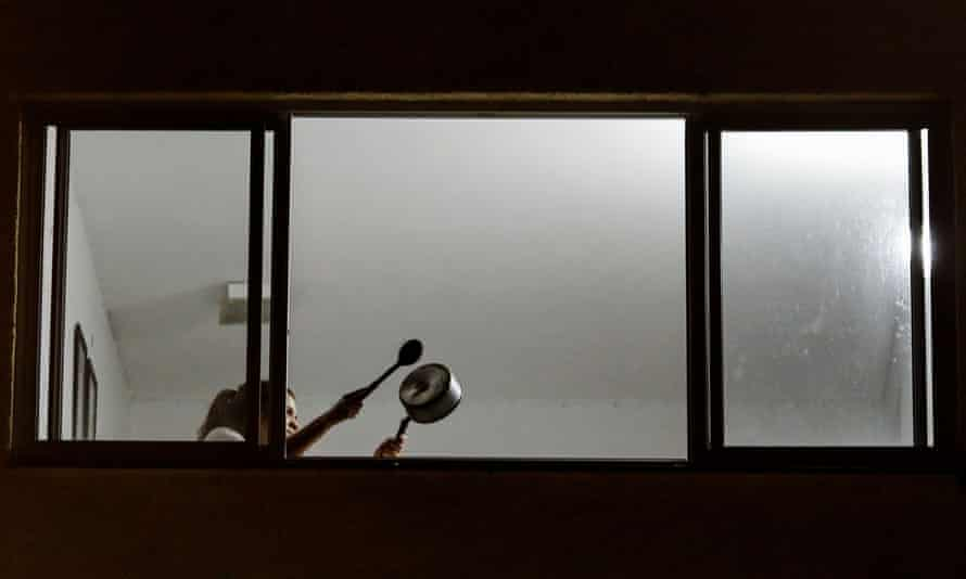 A person beats a pot from a window to protest against Brazil's President Jair Bolsonaro
