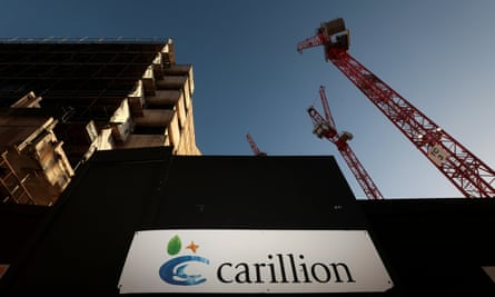 A logo is seen in front of cranes standing on a Carillion construction site