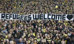 Borussia Dortmund supporters hold a banner showing their support for refugees.