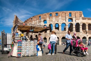 Superb urban fabric … tourists pass the Colosseum in Rome.
