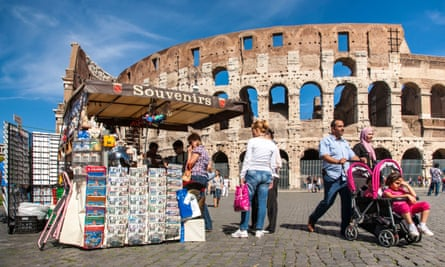 A family of three walks past a souvenir stand outside the Colosseum, Rome, Italy