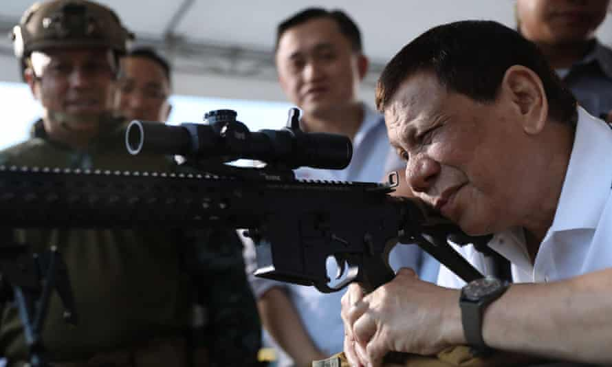 President Duterte fires a rifle at a ceremony