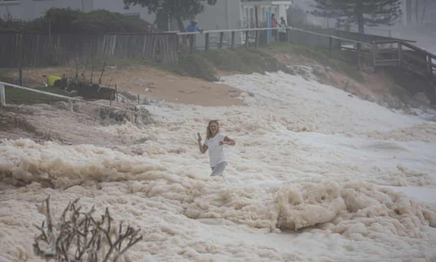 A woman is swamped by a wave on Sydney's northern beaches