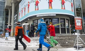 Skiers pass a social distancing sign