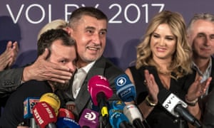 Andrej Babiš embraces a colleague at a press conference in Prague