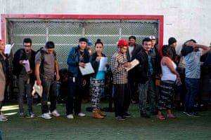 Central American migrants queue as they look for work at a job fair in Tijuana.