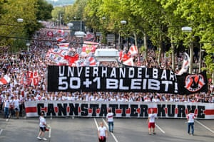 """Thousands of Stuttgart fans march to the stadium ahead of their match against Bayern Munich in 2018. Their banner reads """"Non-negotiable! 50 + 1 remains!"""""""