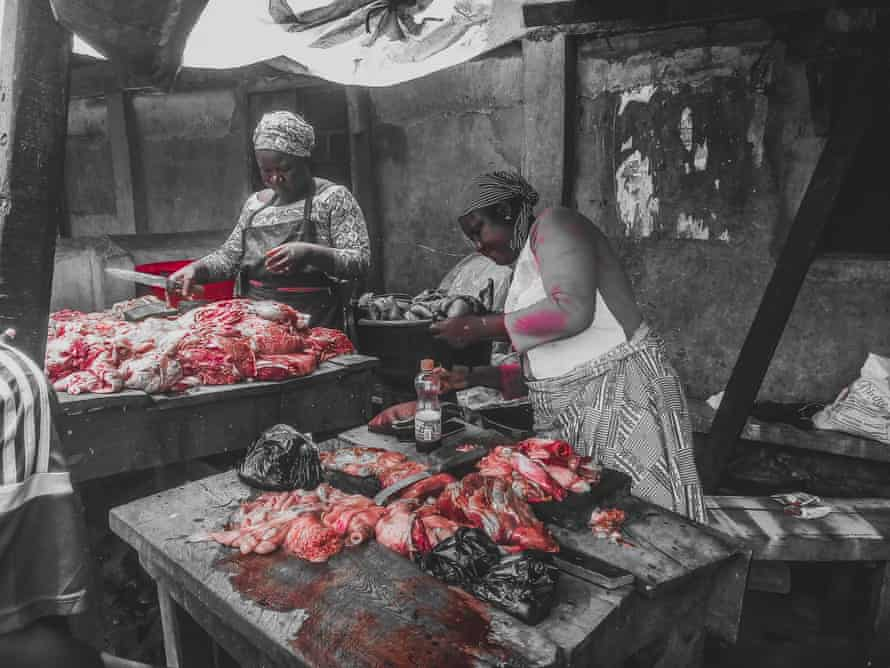 Women prepare meat for sale at the market.