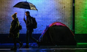 Commuters walk past the tent of a homeless person in London