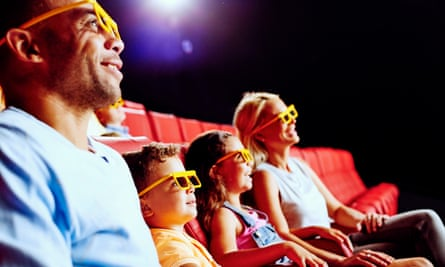 Family of four in the 4D cinema, and wearing viewing glasses, at Legoland Discovery Centre Birmingham, UK.