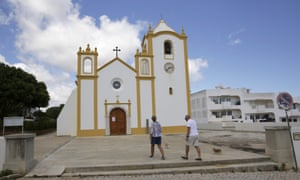 A couple walk in front of the church in Praia da Luz where the McCanns came to pray