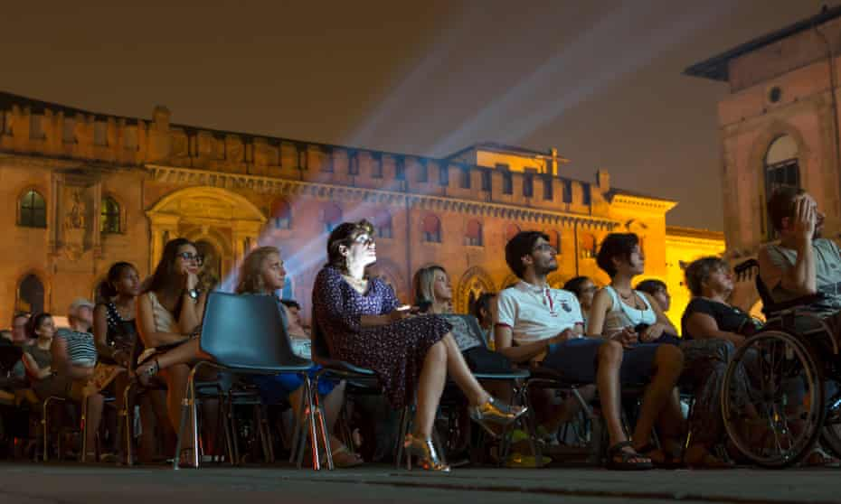 People enjoying a film under the stars at the Piazza Maggiore.