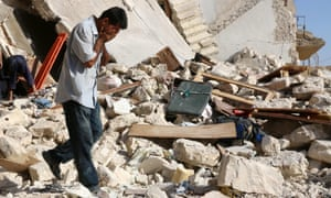 A Syrian man reacts as rescuers look for victims under the rubble of a collapsed building following a reported airstrike on the rebel-held neighbourhood of Sakhur in Aleppo on 19 July.