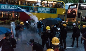 A protester throws back a tear gas round as thousands marched on police headquarters in their fight against the Hong Kong government