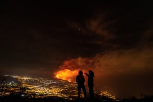 Two women watch the Cumbre Vieja volcanic eruption from a distance in La Palma, Spain