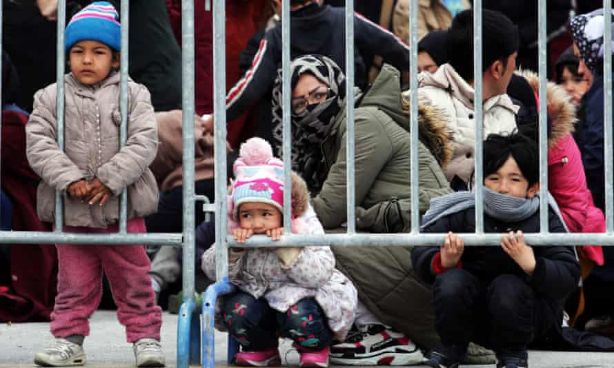 Children and other asylum seekers wait behind bars in Mytilene, Lesbos