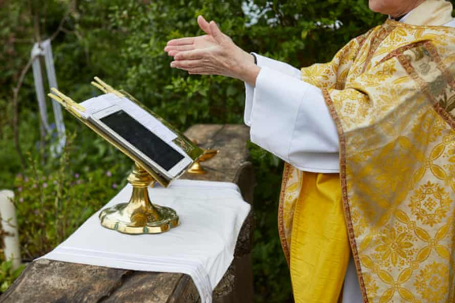 Rev Helen Chandler conducts Sunday Service in her garden outside St Peter and St John, an Anglican church near Lowestoft, Suffolk, May 2020
