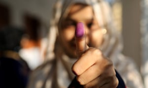 A woman displays her inked thumb after casting her vote.