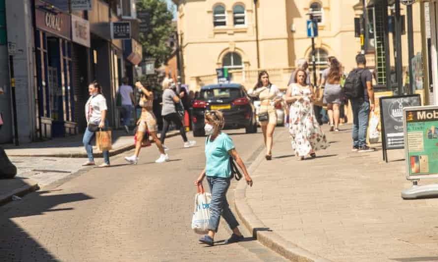 People walking on streets in Bishop's Stortford, some wearing masks outside