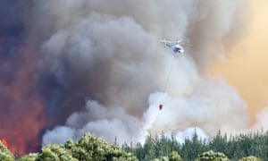 New Zealand helicopters dump water to extinguish a large blaze in the Tasman district
