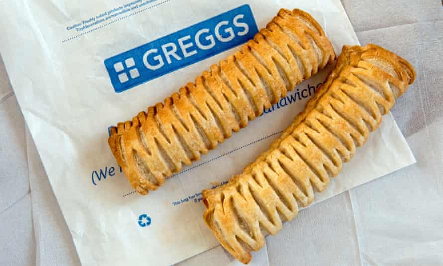 Two Greggs vegan sausage rolls on paper bag with paper napkins behind