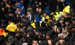 Stewards and police intervene between the two sets of fans at the Carabao Cup semi-final second leg at the Etihad Stadium.