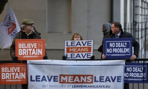 Pro-Brexit campaigners holding signs outside the Houses of Parliament in London.