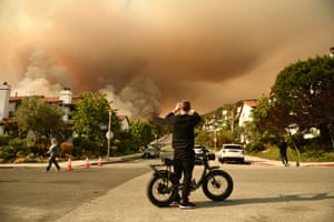 California: A man takes a photo of the plumes of smoke rising from the Palisades fire in Topanga state park near Los Angeles.