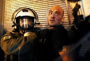 A protester bleeds as he is arrested by riot police following clashes in Athens