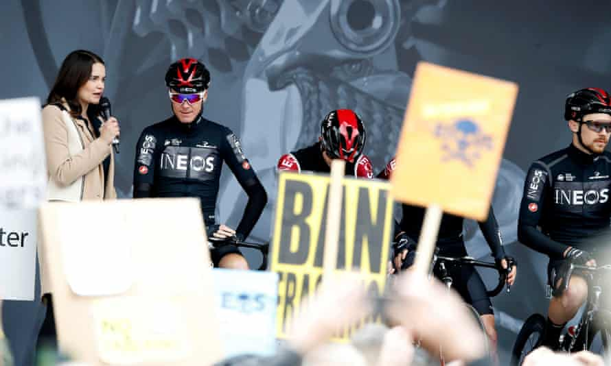 Chris Froome onstage as anti-fracking demonstrators hold up placards.